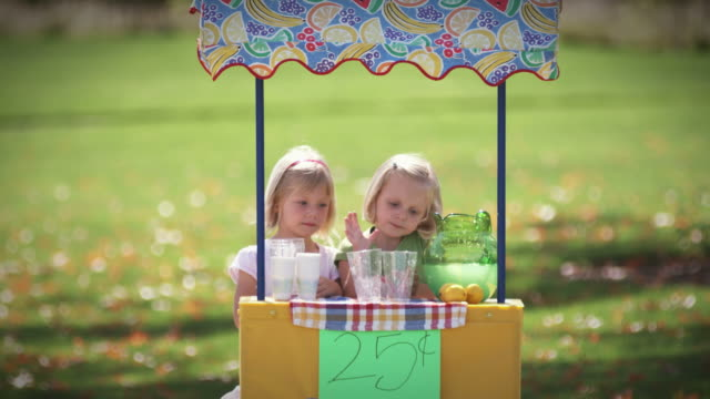 Little girl pours lemonade and spills some. video