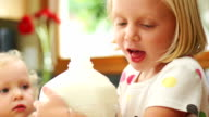 Little girl pours milk for her sister video