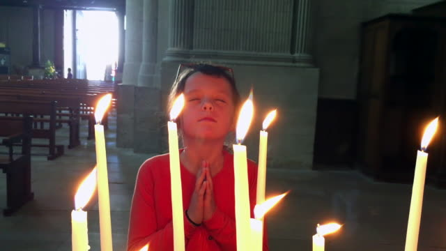 Little girl praying in a large church with hands together behind candles video