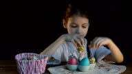 Little girl puts Easter eggs in a basket video