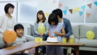 Little Girl Putting Candles on Cake and Family Gathering video