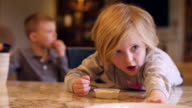 A little girl reaching for food at the kitchen counter, with her brother in the background video
