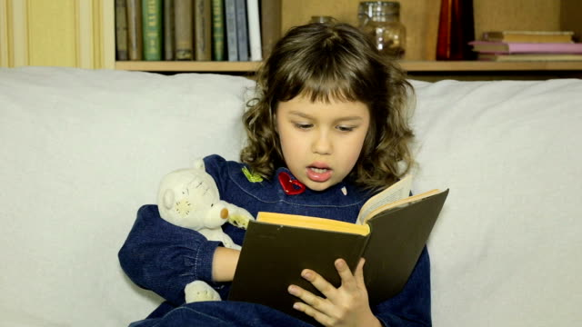 Little girl reading a book aloud teddy bear in the living room on the couch. video