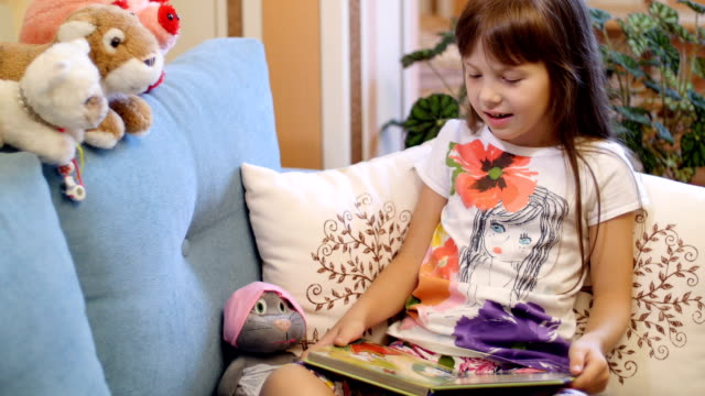 little girl reading a book for their toys video