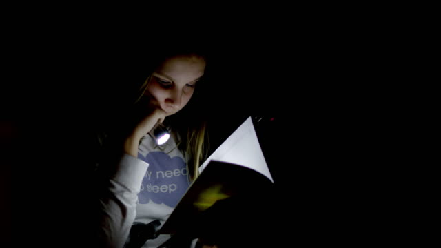 MS Little girl reading a book with flashlight video