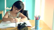 little girl reading and write a book on the table. video