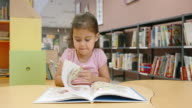 DS Little girl reading at the table in library video