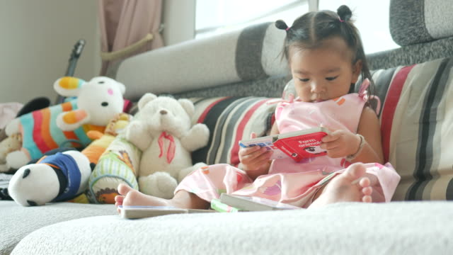 little girl reading book in living room video