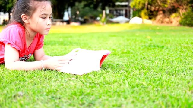 Little girl reading book on green grass. video