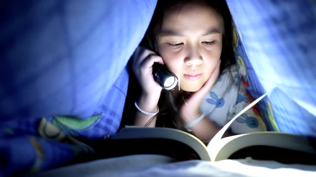 Little girl reading book under the blanket video