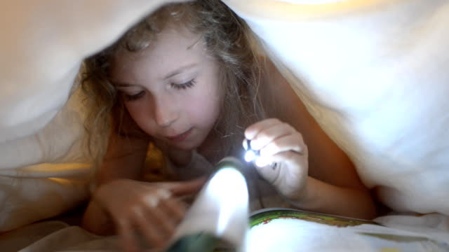 Little girl reading book under the covers. video