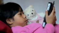 Little Girl Reads Book To Teddy Bear Using Tablet video