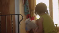 A little girl riding her toy horse through the halls of her house video