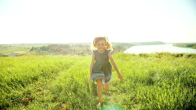 Little girl running on meadow with sunset video