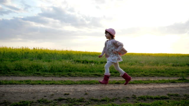 little girl runs along field road, Running child, happy kid having fun outside city, healthy childhood, clean environment video