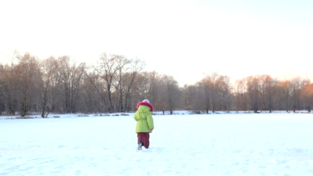 Little girl runs from camera in wintry snowfield video