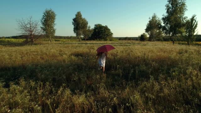 Little girl runs with red umbrella through a field video
