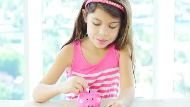 Little girl saving coins in her piggy bank video