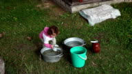 Little girl scooping water with metal mug video