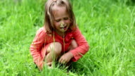 Little girl sits on green grass and crying video