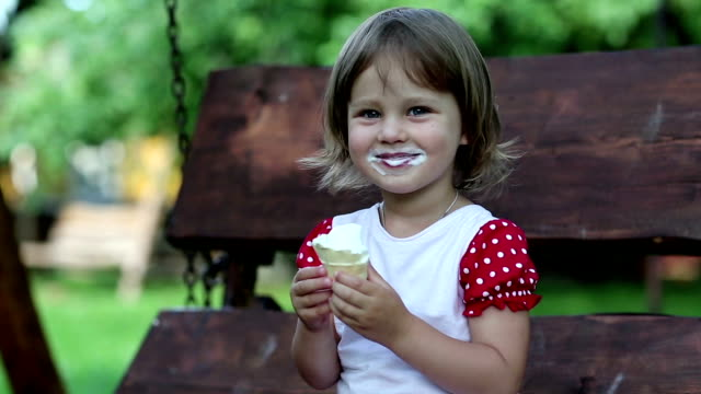 Little girl sits on the bench and eats ice cream video