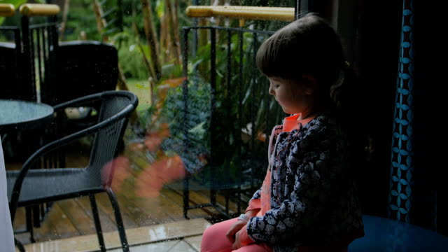 little girl sitting and watching on the backyard from the inside. Wants to play but its heavy rain outside video