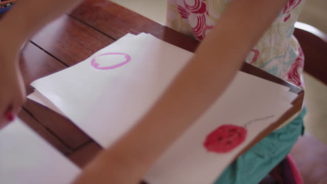 A little girl sitting at a table and coloring with crayons video