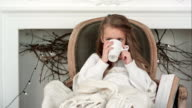 Little girl sitting in a cozy chair wrapped in a blanket drinking tea near Christmas fireplace video