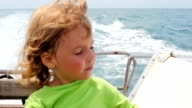 Little girl sitting in going cutter looks at sea video