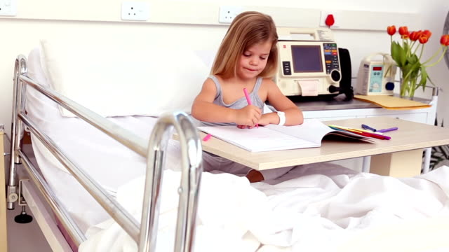 Little girl sitting in hospital bed colouring video