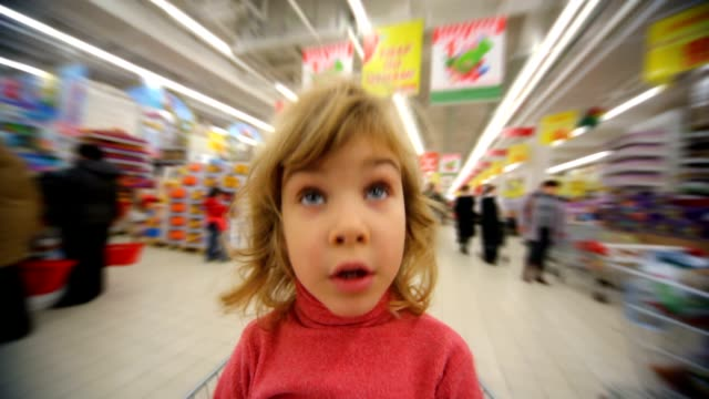 Little girl sitting in moving shopping trolley video