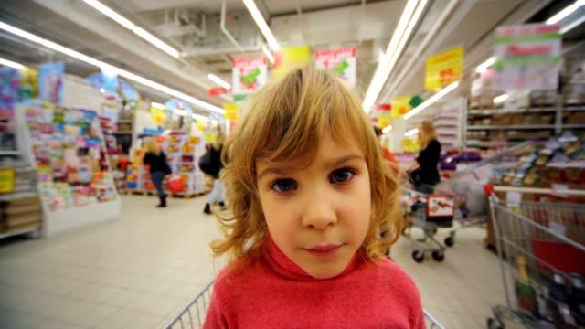 Little girl sitting in shopping trolley video