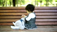 Little girl sitting on a bench. video