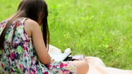 Little girl sitting on grass and playing tablet pc video
