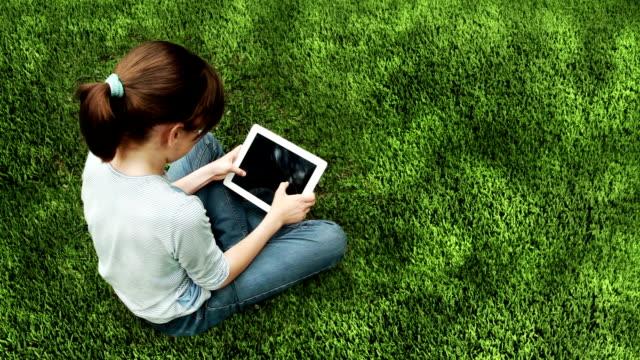 little girl sitting on grass using digital tablet video