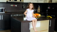 Little girl sitting on the kitchen table video