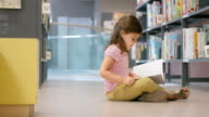 DS Little girl sitting in library and reading video