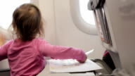 Little girl sitting with exercise book at airplane and looking in illuminator. video