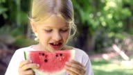 Little girl smiling and eating watermelon fruit outdoors video