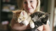 A little girl smiling and holding two kittens in her arms video