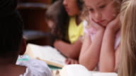 Little girl smiling at camera during library time video