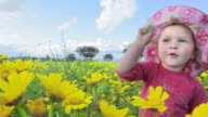 Little girl, spanish blue sky and flowery meadow. Cheerful video. video