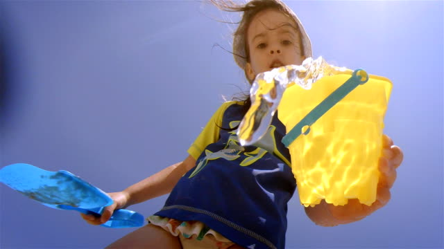Little Girl Splashing Water At Camera While Having Fun At The Beach. video