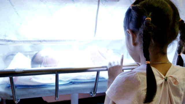 A little girl standing and looking her younger sister in a glass container under the uv light in hospital post delivery room video