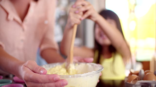Little girl stirring cake ingredients with her Little girl happily stirring cake ingredients in a bowl with a wooden spoon with her mom in their kitchenmom video