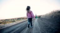Little girl striding along a country road video