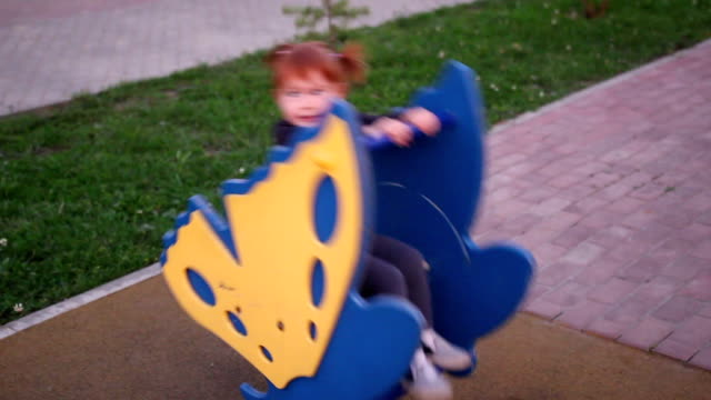 A little girl swinging on a swing in the playground video