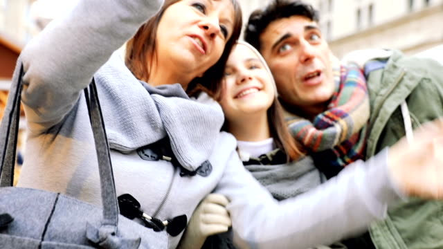 Little girl takes a selfie with parents in Christmas Markets video
