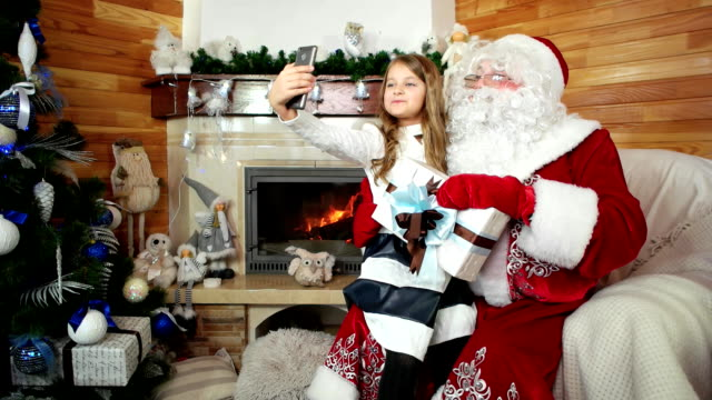little girl taking selfie with santa and her christmas present, kid sitting on santa claus lap video