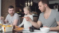 Little girl talking with same-sex parents at breakfast video